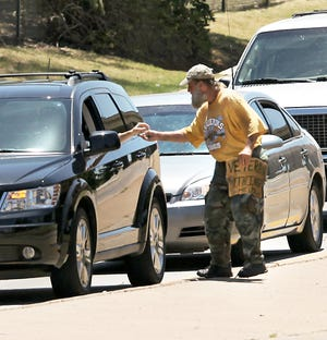 A driver passes money to an Oklahoma City panhandler in 2010. The U.S. Supreme Court on Monday denied the city's attempt to reinstate a 2015 panhandling ordinance that was ruled unconstitutional by a federal appeals court. Critics of the measure said it criminalized poverty.