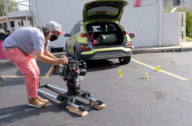 """A masked crew member works on the crime thriller """"Out of Exile"""" at the Flamingo Apartments on NW 23."""