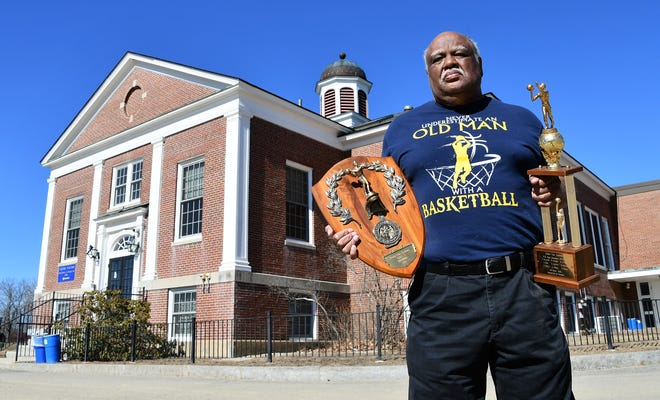 Bill Douglas holds a plaque and trophy that the 1970-71 Austin-Cate boys basketball team received for winning the NHIAA Class S state championship. Douglas is pictured in front of the main Austin-Cate building, which housed administrative offices, classrooms and the gym. The school, which opened in 1833, closed in 1980 and is now an Army National Guard training facility.