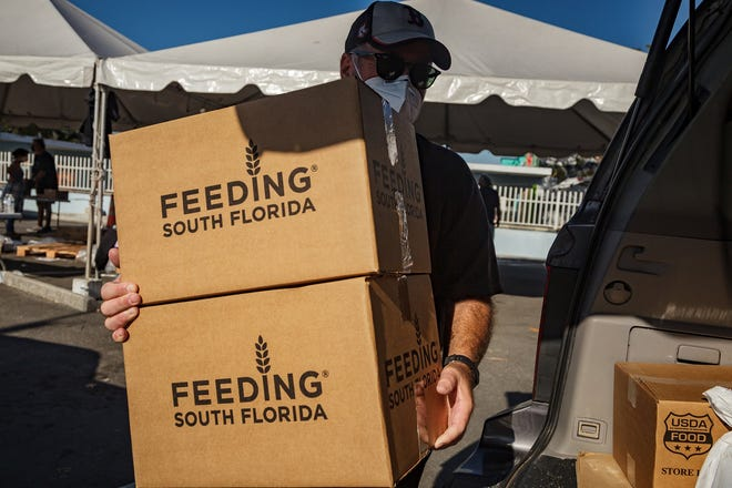 Ira Greenberg of Boynton Beach helps other volunteers load boxes and bags of food at the drive-througha  Feeding South Florida event at the Hatch 1121 parking lot in Lake Worth Beach in late March.