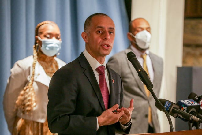 Providence Mayor Jorge Elorza announces the completion of a report on racism in Rhode Island's history. Listening behind him are Shawndell Burney-Speaks and Marco McWilliams, associate director of The Center for Reconciliation.