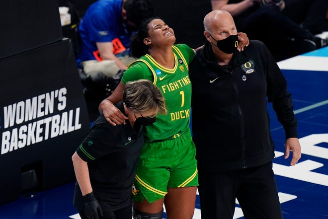 Oregon's Nyara Sabally (1) is helped off the court by coach Kelly Graves after suffering an ankle injury during the third quarter of Sunday's 60-42 loss to Louisville in a Sweet 16 game of the NCAA Tournament in San Antonio.