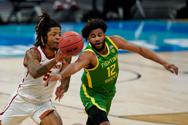 Oregon guard LJ Figueroa (12) tries to steal the ball from Southern California guard Isaiah White, left, during the first half of a Sweet 16 game in the NCAA men's college basketball tournament at Bankers Life Fieldhouse, Sunday, March 28, 2021, in Indianapolis. (AP Photo/Jeff Roberson)