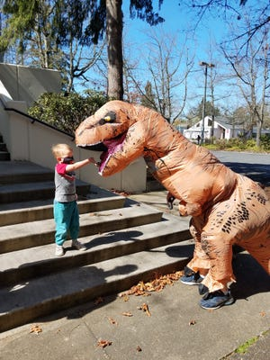 Springfield librarian Mark Riddle, dressed as a dinosaur, meets with Dexter Kreitlow as part of a spring break nonfiction book giveaway at Springfield Public Library in March 2020.