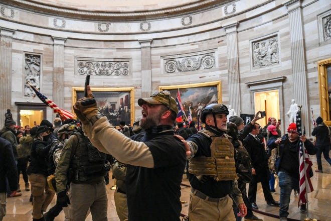 Graydon Young, of Englewood, right in helmet, is seen during the invasion of the U.S. Capitol on Jan. 6, 2021. He has been in jail since his arrest Feb. 15.