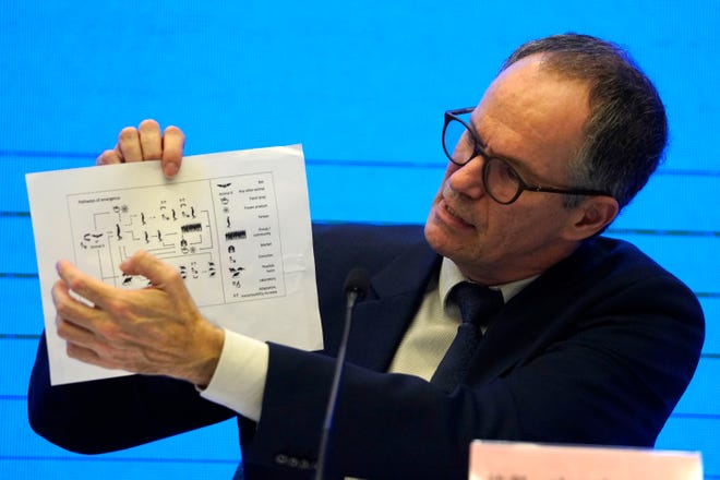 """FILE - In this Feb. 9, 2021, file photo, Peter Ben Embarek of the World Health Organization team holds up a chart showing pathways of transmission of the virus during a joint news conference at the end of the WHO mission in Wuhan in central China's Hubei province. A joint WHO-China study on the origins of COVID-19 says that transmission of the virus from bats to humans through another animal is the most likely scenario and that a lab leak is """"extremely unlikely,"""" according to a draft copy obtained by The Associated Press. (AP Photo/Ng Han Guan, File)"""