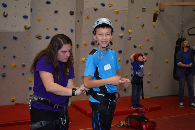 Siskiyou Family YMCA worker Ashley Cox helps someone at the rock wall pre-COVID-19. Due to restrictions being lifted in the state, the YMCA was recently allowed to reopen indoors again.