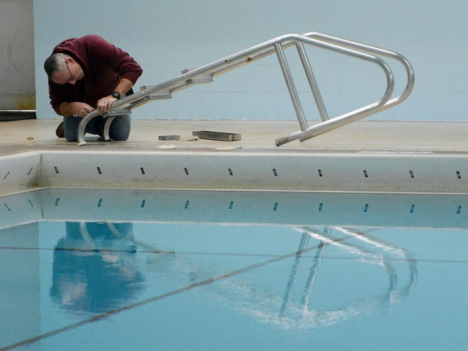 Ron Roberts, maintenance lead at Plainfield Town Hall, replaces a refurbished step on a pool ladder for the Town Hall swimming pool Monday that may reopen to the public in a month.