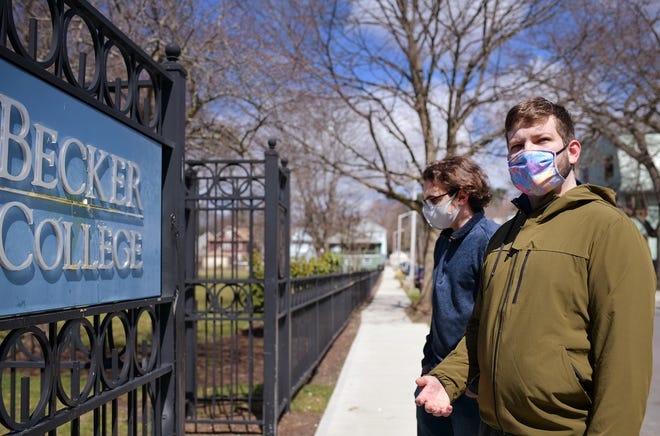 Nicholas Lord and Joseph Ressler, Becker College freshmen, stand near a sign on the Worcester campus Monday. The students said they woke up to emails announcing the permanent closing of the school.
