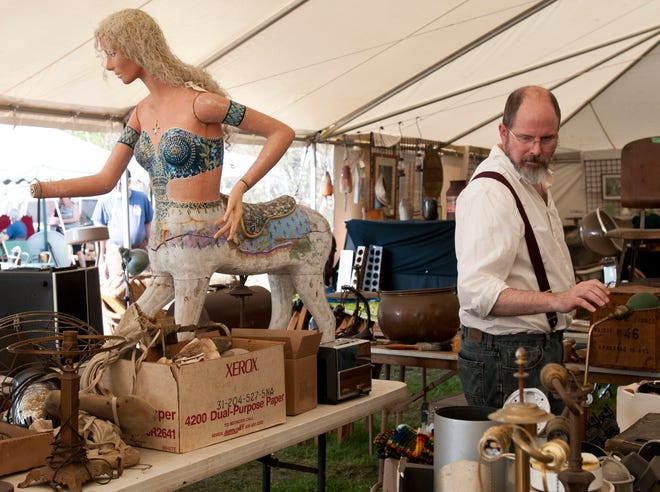 A man walks by a mannequin carousel horse hybrid as he peruses the tent at the Brimfield Antique Flea Markets in May 2016.
