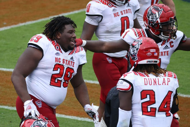 Oct 10, 2020; Charlottesville, Virginia, USA; North Carolina State Wolfpack defensive tackle Alim McNeill (29) celebrates with teammates after returning an interception for a touchdown against the Virginia Cavaliers in the fourth quarter at Scott Stadium. Mandatory Credit: Geoff Burke-USA TODAY Sports