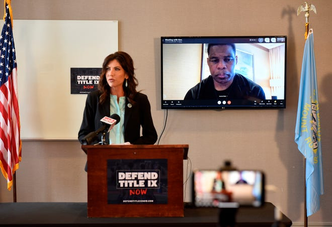 "South Dakota Gov. Kristi Noem in Sioux Falls on Monday, March, 22, 2021, discusses an initiative for ""protecting fairness in women's sports"" by banning transgender women from participating in women's sports leagues. Herschel Walker, a retired professional football player, joined the news conference through a video call. (Argus Leader via AP)"