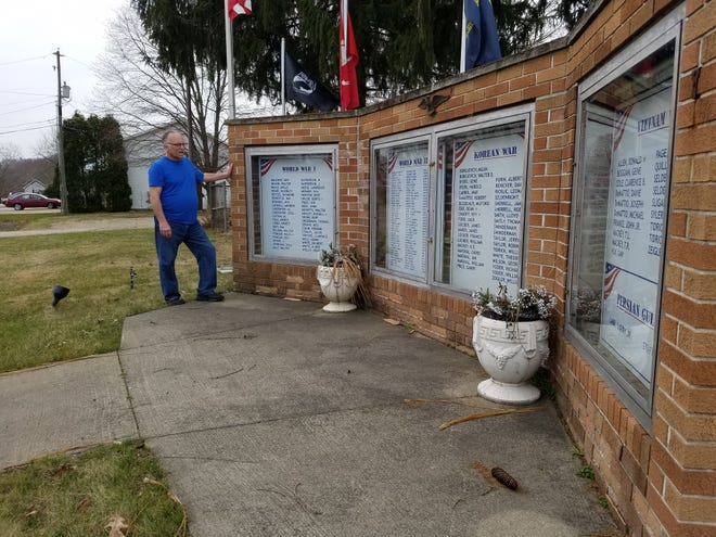 Midvale Mayor Larry Kopp stands with the village's deteriorating war memorial. Repairs to the memorial's brick are among the items to be funded by a 0.5% income tax increase sought by village government in the May 4 primary election.