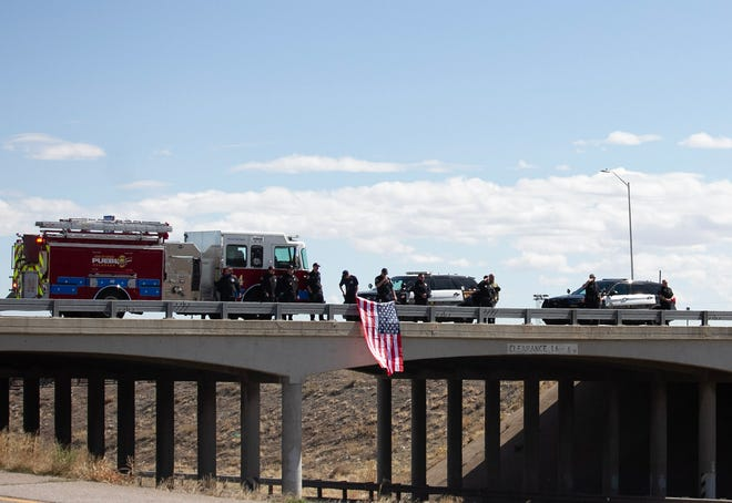 Firefighters unfurled a flag on the overpass, and officers saluted as the family passed through the city of Pueblo on Saturday, March 27.