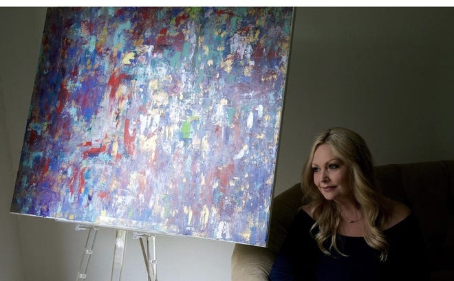 """Jill Moody-Ledbetter sits next to her painting """"On Fire,"""" that is on display in Milano, Italy."""