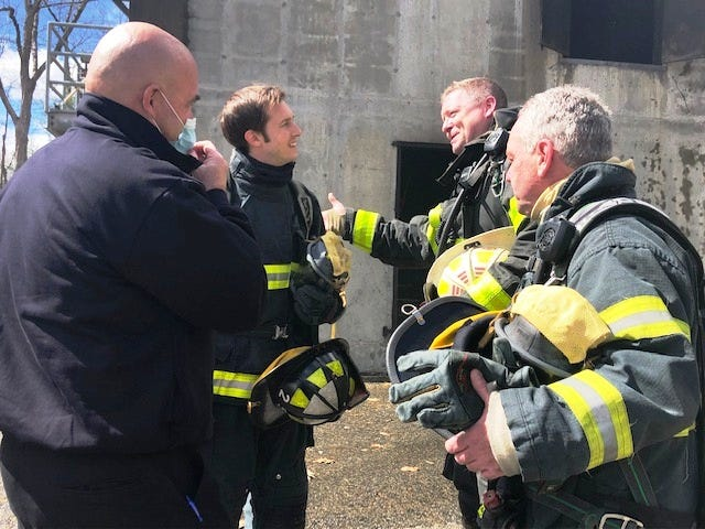 Congressman Jake Auchincloss (background, left) talks with Franklin Fire's Battalion Chief Chuck Allen (background, right), state Rep. Jeff Roy, D-Franklin (foreground, right) and Franklin Fire Chief James McLaughlin (foreground, left) after participating  in a live burn training exercise with the Franklin Fire Department at the Milford Fire Department's training structure on March 29.