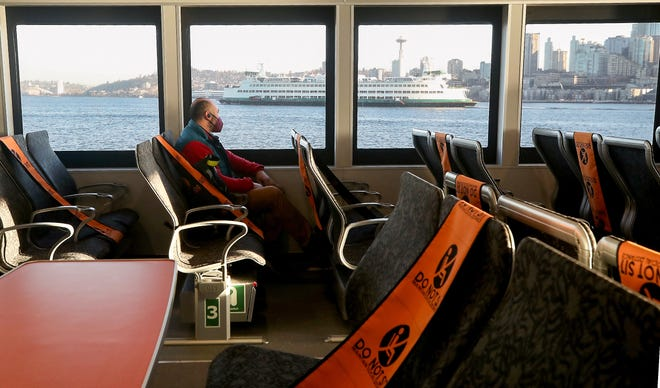 Ari Troka watches a Washington State Ferry pass by as Kitsap Transit's M/V Enetai heads for the dock in Seattle on Monday, the first day of regular service on the route for Kitsap Transit. Troka said his family relocated from Seattle to South Kitsap in anticipation of fast ferry service.