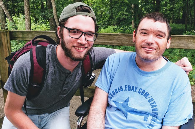 Camp volunteer Colin Maffett with camper MJ at the nature center at Camp Echoing Hills. The nature center is nestled within nature trails and provides different sensory experiences in a calm environment.