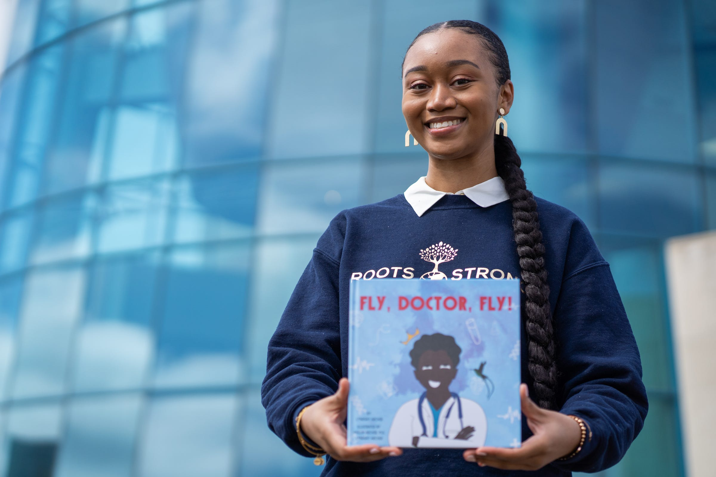 """Lyndsay Archer, 23, of Southfield shows the children's book she recently wrote titled, """"Fly, Doctor, Fly!"""" outside of the Southfield Public Library in Southfield on Friday, March 26, 2021. Archer co-illustrated the book with the inspiration behind it, her dad, Phillip. The book highlights Black and brown doctors. Archer is the founder of nonprofit, Roots Strong, which works toward serving youth locally and globally, centered around education, literacy and health.   Her nonprofit has built two libraries in Jamaica."""