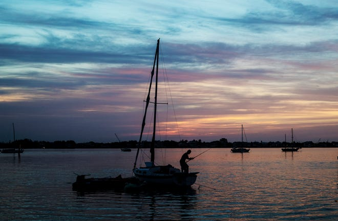 Scenes from Bowditch Point Park on Fort Myers Beach during moon set and sunrise on Monday.