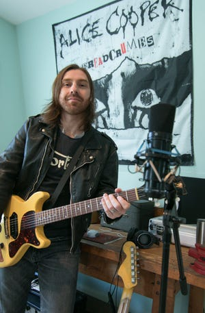"""Garret Bielaniec, who has performed with world-renown rock musicians, recently played on Alice Cooper's latest release, """"Detroit Stories,"""" which was recorded in Royal Oak. Bielaniec, a Howell native, poses in his Howell studio Monday, March 29, 2021."""