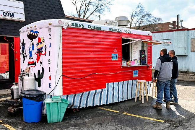 Customers order food at Maria's Cuisine Mexican food truck on Wednesday, March 24, 2021, in Old Town Lansing.