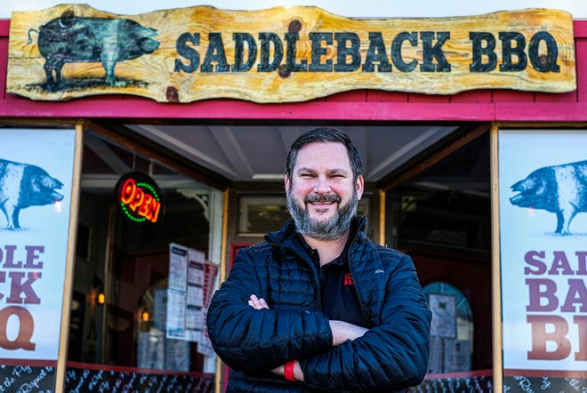 Travis Stoliker, co-owner of Saddleback BBQ, stands in front of his REO Town restaurant Monday, March 29, 2021. Stoliker and co-owner Matt Gillett began paying off the lunch debt of students in area schools. Then the effort snowballed.