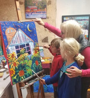 Artist Susan Hale gives a painting demonstration to two young painters during a previous Covered Bridge Art Studio tour, put on by the Cedarburg Artists' Guild.