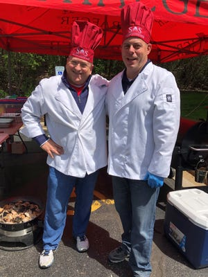 Jack Ruskin, Specialized Accounting Services LLC business development director, and Chief Executive Officer Jamie Hogan grill lunch for employees. The company's core values include living well and having fun.