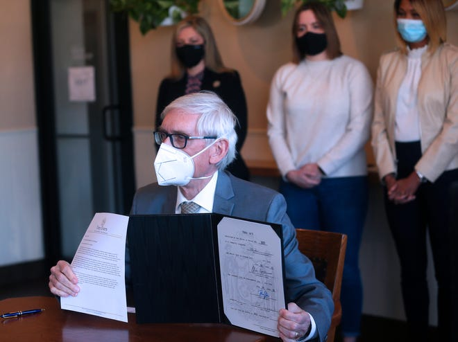 Wisconsin Gov. Tony Evers holds up his veto of a Republican bill to control how $3.2 billion in federal stimulus funding is spent  Monday, March 29, 2021, at Miss Molly's Cafe & Pastry Shop at 9201 W. Center St. in Milwaukee. Standing behind Evers, from left, are state Rep. Robyn Vining,  and business owners Molly Sullivan of Miss Molly's and Beth Ridley of Beth Ridley Consulting.