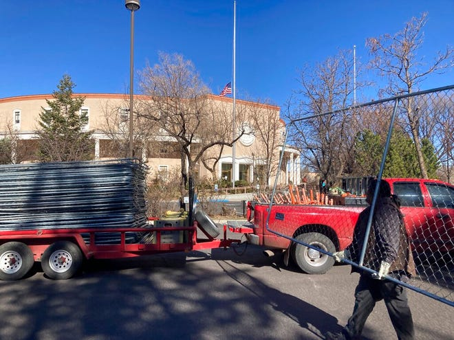 Workers remove segments of the chain-link fence around the New Mexico state capitol in Santa Fe on Saturday, March 27, 2021.