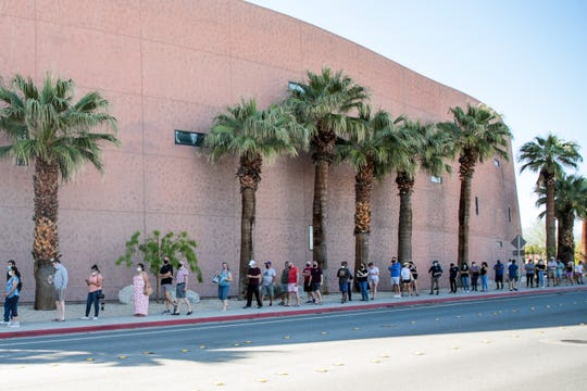 People wait in a line outside the Palm Springs Convention Center to receive the COVID-19 vaccine on Monday, March 29, 2021, in Palm Springs, Calif.  Conventions and trade shows will return to the area and the vaccination center will be shut down by the end of June.