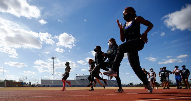 Mar. 4, 2021; Chandler, Arizona, USA; Chandler's track team warms up with stretches during a track practice at Chandler High School. Mandatory Credit: Patrick Breen-Arizona Republic
