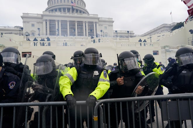 Police try to hold back protesters who gather to storm the Capitol and halt a joint session of the 117th Congress on Wednesday, Jan. 6, 2021, in Washington, D.C. (Kent Nishimura/Los Angeles Times/TNS)