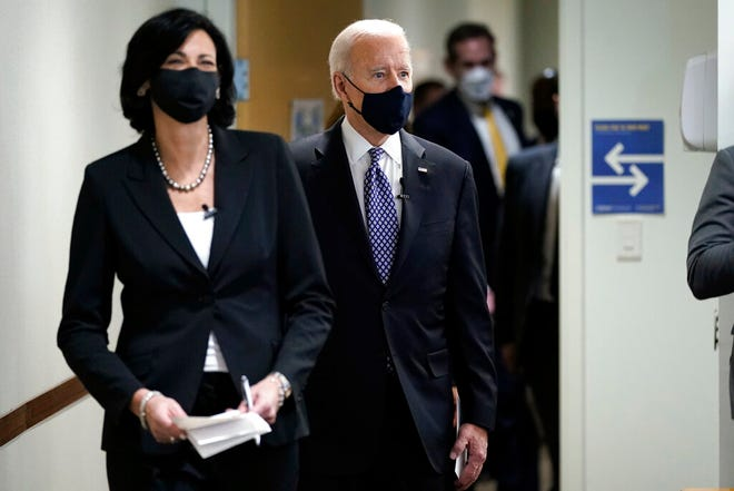 """In this March 19, 2021, photo, Dr. Rochelle Walensky, director of the Centers for Disease Control and Prevention, leads President Joe Biden into the room for a COVID-19 briefing at the headquarters for the CDC Atlanta. Walensky is making an impassioned plea to Americans not to let their guard down in the fight against COVID-19. She warned on March 29 of a potential """"fourth wave"""" of the virus. (AP Photo/Patrick Semansky)"""