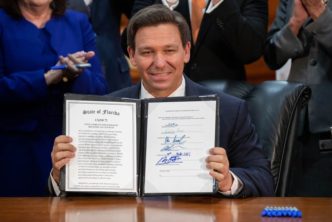 Gov. Ron DeSantis smiles after signing into law SB 72, which gives COVID liability protections to Florida businesses, in the Cabinet meeting room of the Capitol Monday, March 29, 2021.