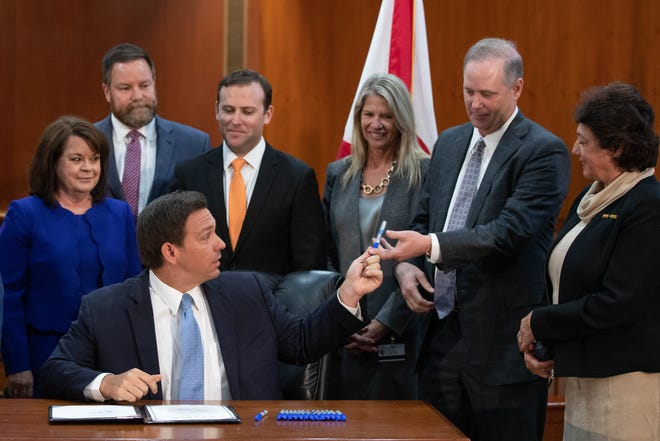 Gov. Ron DeSantis hands a blue Sharpie to Senate President Wilton Simpson after using it to sign SB 72, a bill that gives COVID liability protections to Florida businesses, into law in the Cabinet meeting room of the Capitol Monday, March 29, 2021.