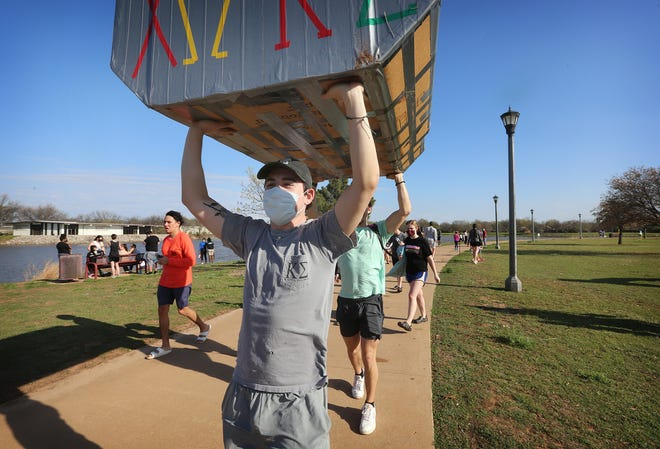 Logan Spikes, mass communication sophomore, helps to carry the Kappa Sigma boat away after the cardboard boat race on Sikes Lake as part of StangFest 2021, March 27, 2021. Photo by Bradley Wilson