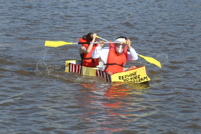 Juan Parra, senior in graphic design, and Rebekah McDaniel, freshman in radiology, bring the Redwine Honors Program boat in for an early lead at the cardboard boat race on Sikes Lake as part of StangFest 2021, March 27, 2021. Redwine Honors Program and Kappa Pi Honorary Society had the sturdiest of the cardboard boats this year, lasting 4:33:23 on the water of Sikes Lake.