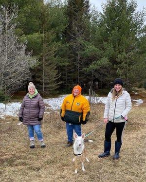 Rebecca, Susan, Rachel, and Joy the dog walking around the cabin property.