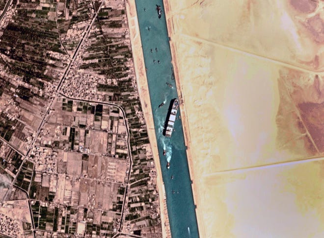 """This satellite photo from Planet Labs Inc. shows the Ever Given cargo ship stuck in Egypt's Suez Canal Monday, March 29, 2021. Engineers on Monday """"partially refloated"""" the colossal container ship that continues to block traffic through the Suez Canal, authorities said, without providing further details about when the vessel would be set free."""