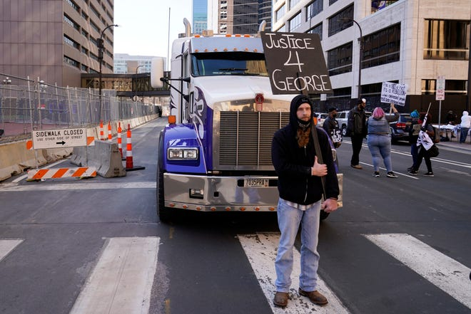 A unidentified protester blocks a truck on a street next to the Hennepin County Government Center as protesters held vehicles at bay until they honked their horns Monday, March 29, 2021, in Minneapolis. The trial for former Minneapolis police officer Derek Chauvin began with opening statements from both sides. Chauvin is charged with murder in the death of George Floyd during an arrest last May in Minneapolis. (AP Photo/Jim Mone) ORG XMIT: M109