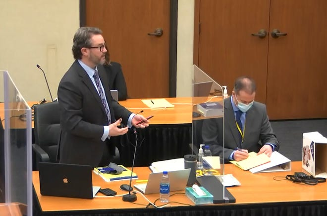Defense attorney Eric Nelson, left, accompanied by former Minneapolis police officer Derek Chauvin, speaks as Hennepin County Judge Peter Cahill presides at the opening of Chauvin's trial Monday.