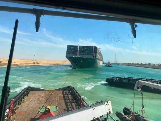 På dette bildet utgitt av Suez Canal Authority, seiler Evergreen, et Panama-flagget lasteskip med Suez Canal-slepebåter mandag 29. mars 2021 i Egypt.
