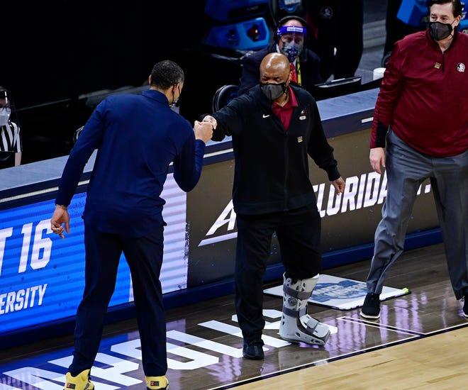 Florida State head coach Leonard Hamilton, center, fist bumps Michigan head coach Juwan Howard, left, following the Wolverines' victory in the Sweet 16.