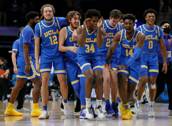 David Singleton of the UCLA Bruins and Kenneth Nwuba celebrate with teammates after defeating the Alabama Crimson Tide 88-78 in overtime in the Sweet Sixteen round game of the 2021 NCAA Men's Basketball Tournament at Hinkle Fieldhouse.