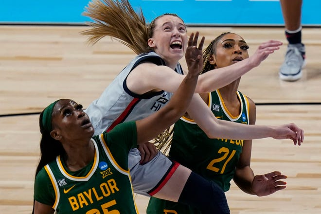 UConn guard Paige Bueckers, center, drives to the basket between Baylor defenders Queen Egbo, left, and DiJonai Carrington during UConn's win in the Elite Eight round of the women's NCAA tournament at the Alamodome in San Antonio on Monday. Bueckers led the Huskies with 28 points.