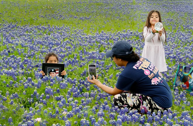 Kathy Torrez, center, takes a photo of her 3-year-old daughter, Lorelei, while 4-year-old Ariela holds a globe in a field of bluebonnets. The Bastrop family once took photos in this spot with the girls' dad, Raul Rudy Torrez III. But on Tuesday, Ariela's globe held a photo of her late father, who passed away since their last visit to the bluebonnets.
