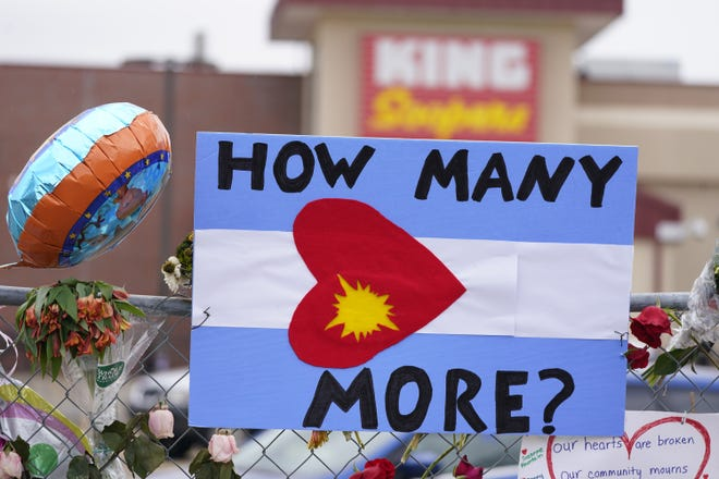 In this March 26 photo, a sign tops the temporary fence line outside the parking lot of a King Soopers grocery store, the site of a mass shooting in which 10 people died in Boulder, Colo. [AP Photo/David Zalubowski]