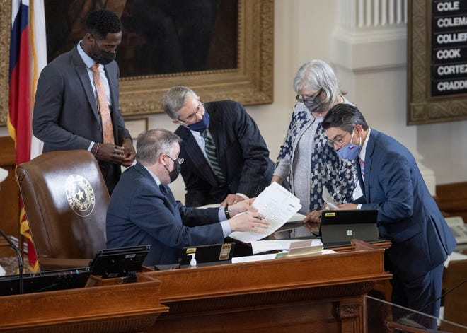 State Rep. Chris Paddie, R - Marshall, right, works on his House Bill 11 in the House chamber at the Capitol on March 30. The bill would require power-generating facilities to prepare for extreme weather emergencies.